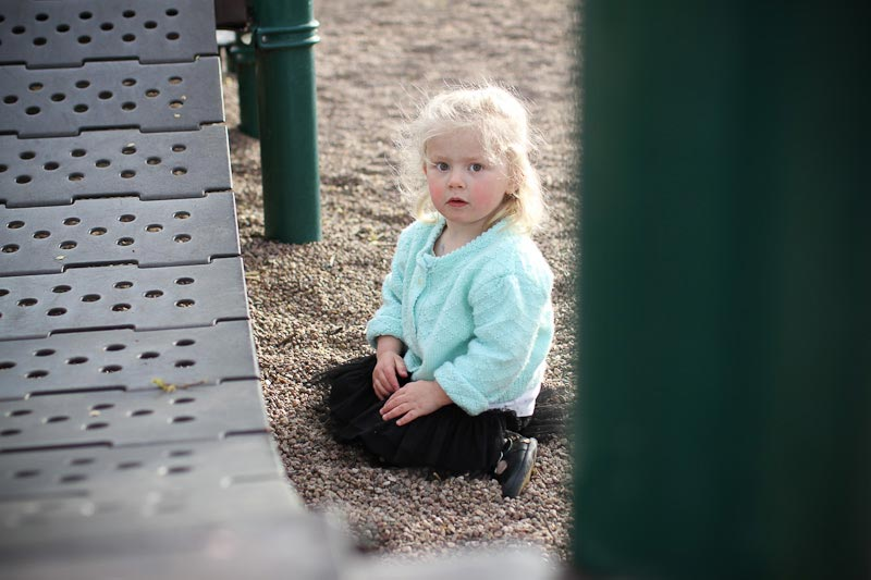 photograph of child sitting on playground